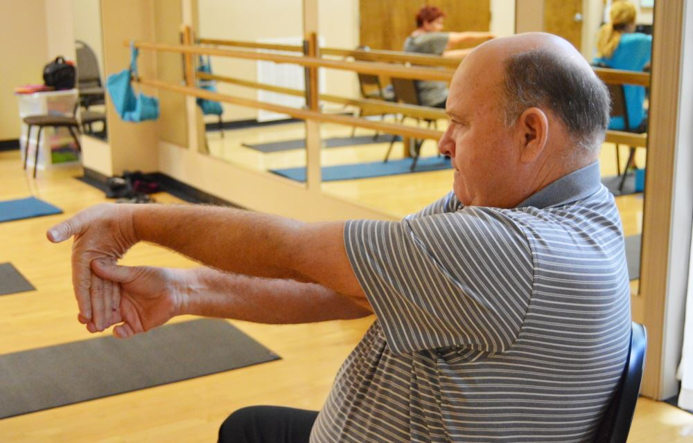 A man participates in a chair yoga class.