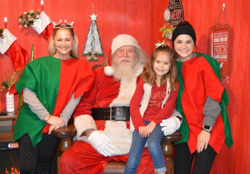 Elves and a child gather with Santa at the Santa House