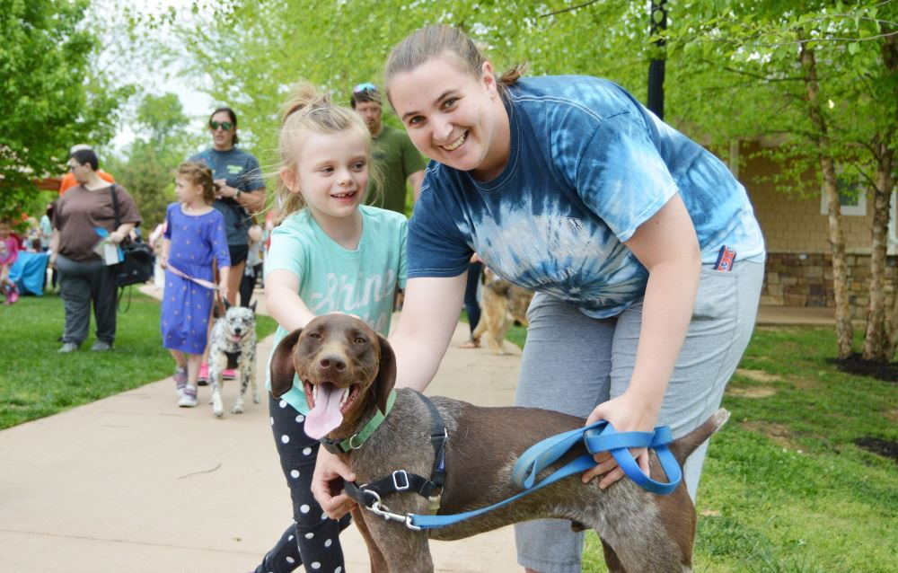 A mother, daughter and their dog enjoy Dogapalooza at Dogwood Park.