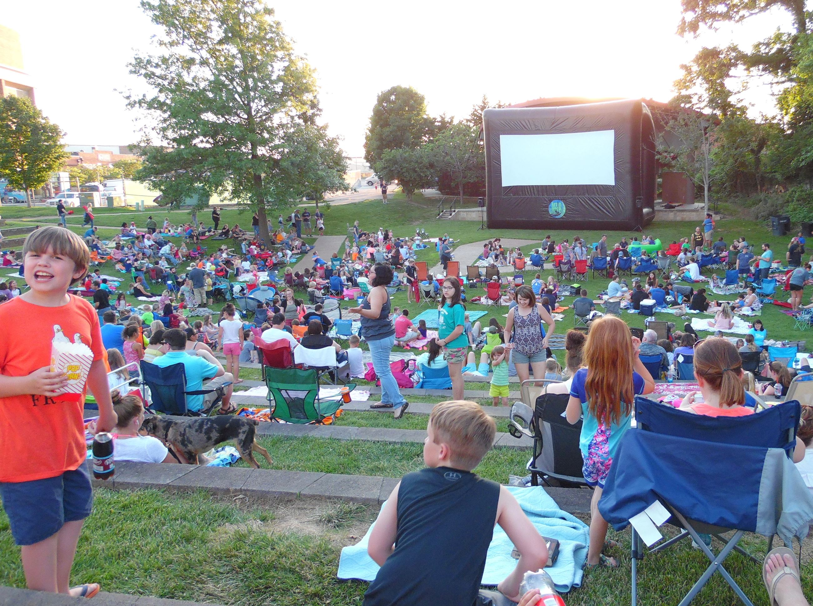 A crowd gathers at Dogwood Park for After Dark Movies in the Park.