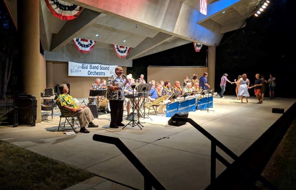 The band plays and people dance at a Big Band Sound Orchestra concert at Dogwood Park.