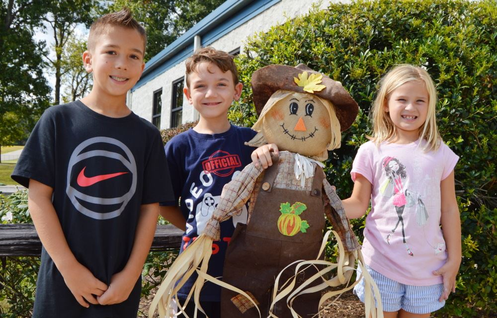 Children stand with a scarecrow during fall break camp.
