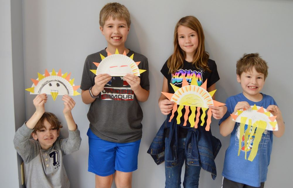 Children show their artwork at spring camp.