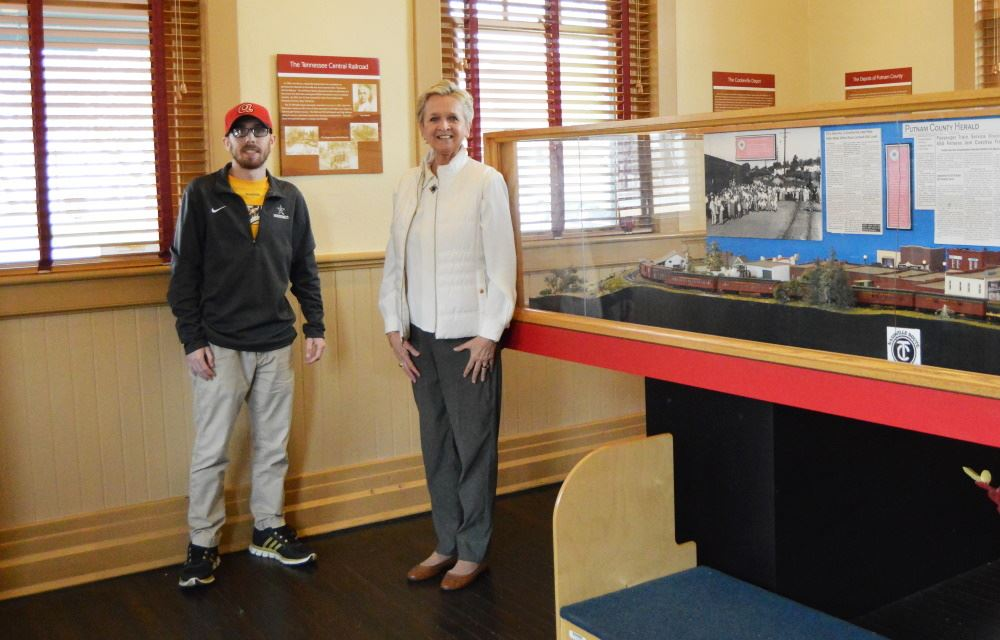 Two docents stand next to the model train at the Depot.